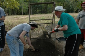 Student and Rabbi Blau, right, shovel dirt to be used in mixing cement for village library.