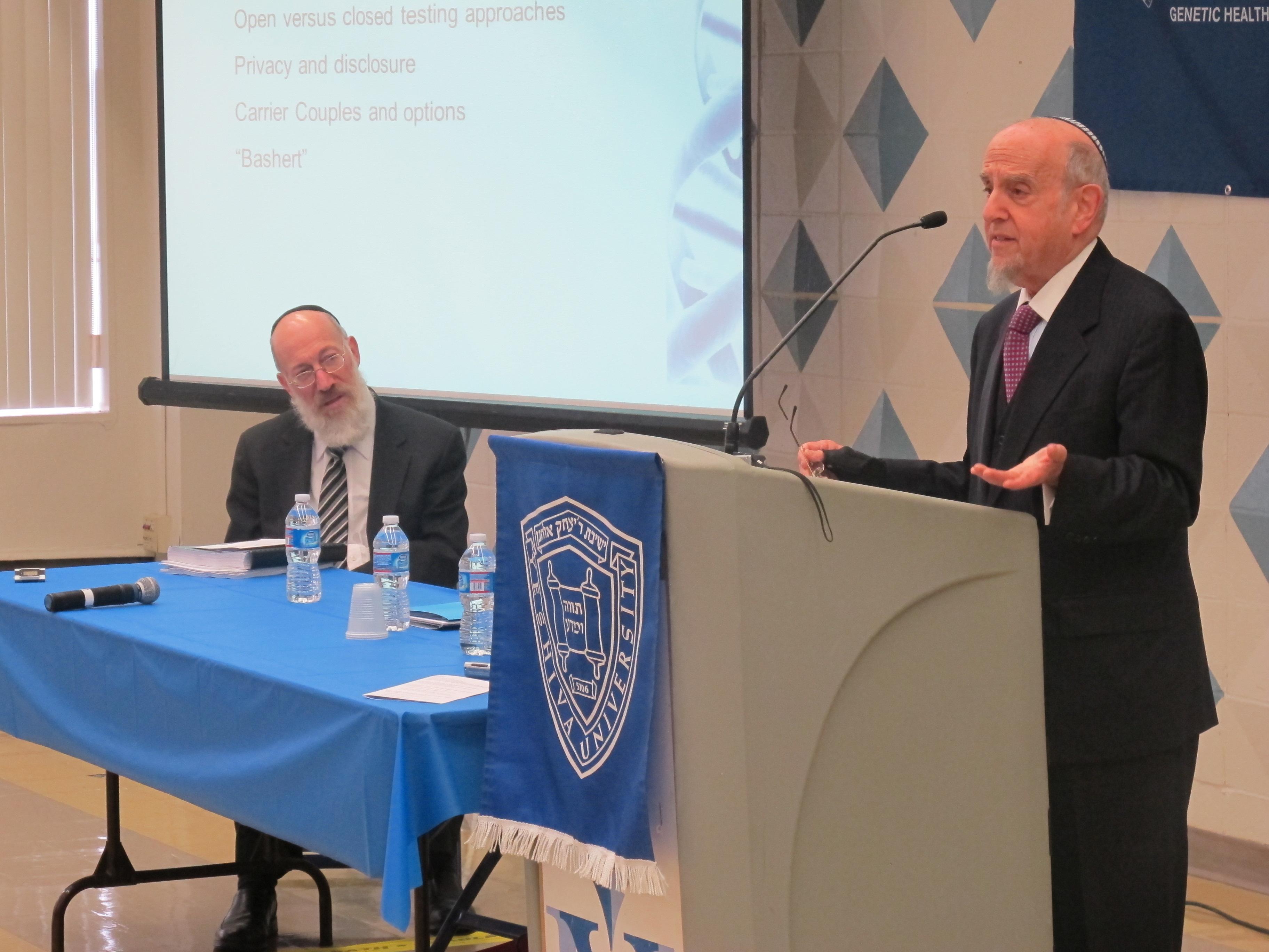 Rabbi Lookstein addresses the symposium crowd. Rabbi Willig looks on.