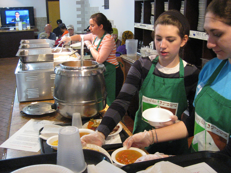 Shaina Joyandeh, Lila Bleich, and Nechama Rollhaus prepare food at a Masbia soup kitchen in Brooklyn, NY.