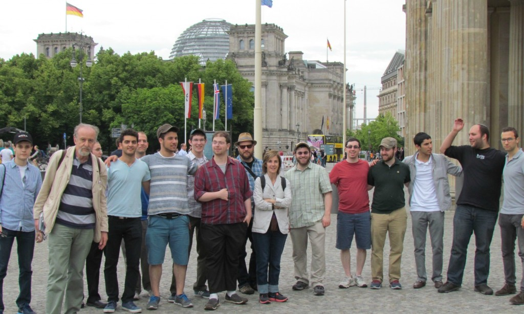 Students in a plaza across the street from the Holocaust memorial. In the background is the ceiling of the Bundestag (the German Parliament) and part of the Brandenburg Gate.