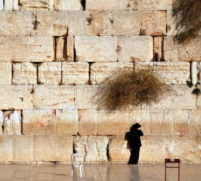 Jewish man is praying at the western wall in the old city in Jerusalem, Israel.