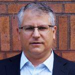 Dr. Joshua Zimmerman against a brick wall