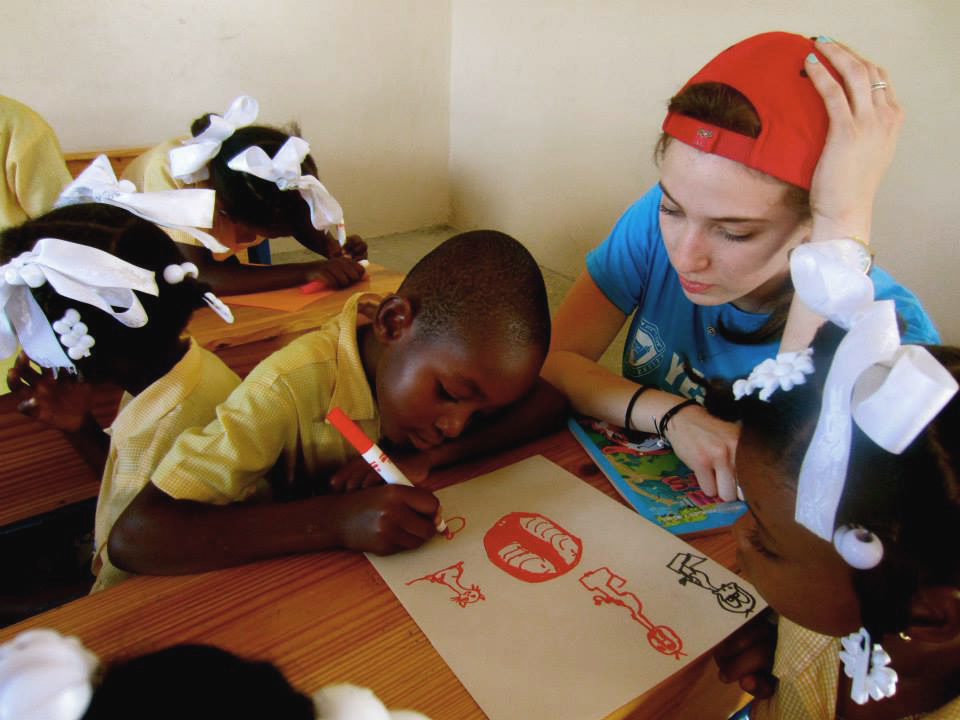 Esther Shmunis, a participant on the Haiti mission, works on an art project with a student in Zoranje.