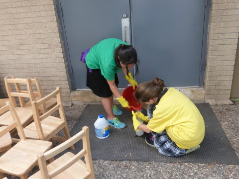 Student Ariella Levie, left, and a middle school student from the Robert M. Beren Academy get ready to disinfect all of the chairs from the Goldberg Montessori School housed in United Orthodox Synagogues, which was destroyed.