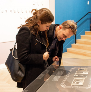 Lost & Found: A Family Album. Two people looking at photos in a display case.
