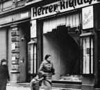 Woman and child passing smashed shop windows after Kristallnacht in Magdeburg, Germany, November 1938. (Bundesarchiv/Friedrich, H./CC-BY-SA 3.0)