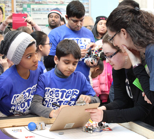 FIRST Robotics Competition - Referees working with two young competitors