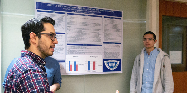 Psychology students present their poster on emotionality