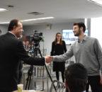 Mark Gjonaj shakes hands with a student.