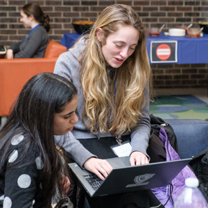 Two women coding on computers