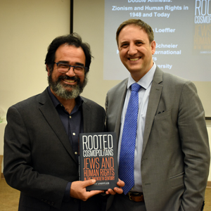 Dr. Ronnie Perelis and Dr. James Loeffler standing holding Dr. Loeffler's book