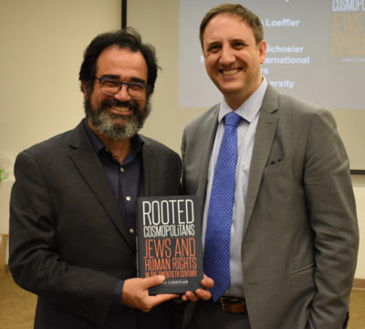 Dr. Ronnie Perelis and Dr. James Loeffler stand side by side holding Dr. Loeffler's book.