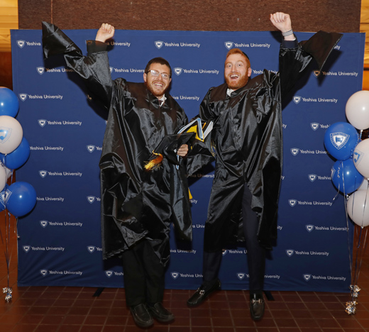 Two men leaping in joy at receiving their diplomas