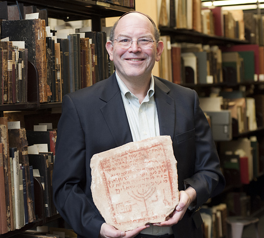 Steven Fine, professor of Jewish History, with ancient Biblical tombstone. It's a limestone gravestone from Zoar. The stone is from 430 C.E.—some 360 years after the destruction of the Second Temple.