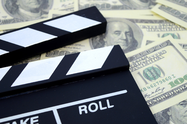 A conceptual image focused on the movie industry and the money it can produce using a clapboard and American cash as a background.