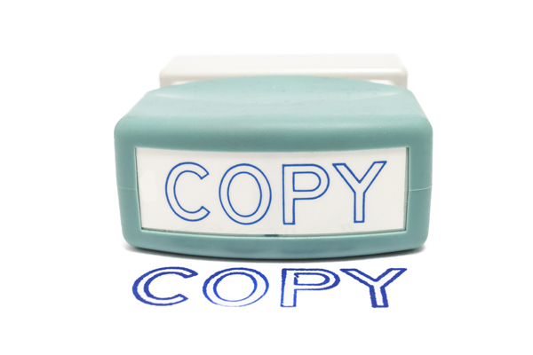 """Self-inking rubber Copy stamp next to the word """"COPY"""" stamped on paper, isolated on white."""