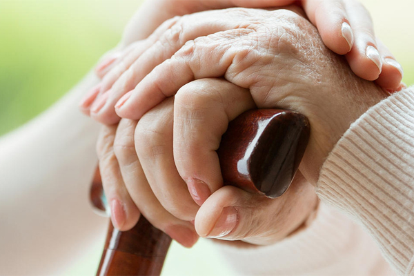 Picture of a hand on an older person's hand resting on the head of cane
