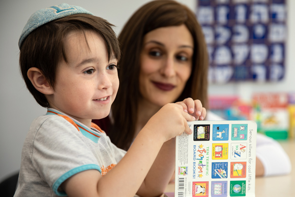 Young child and mother learn together. He has book open, and she looks lovingly at him.