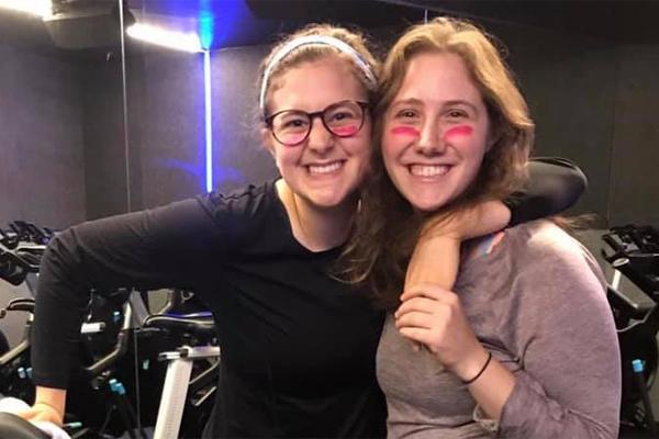Two women pose in the gym for Sweat 4 Tzedakah