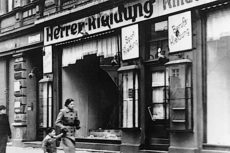 Bombed out window of store with woman and child hurrying by