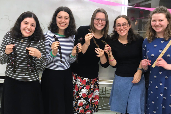 Four women hold their cut hair for the donation event.