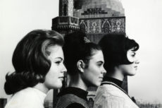 Three women stand in profile with Zysman Hall in the background