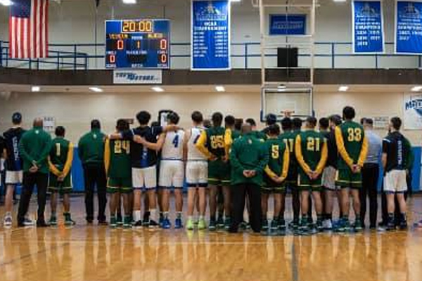 Basketball players from YU and NJCU have a moment of silence.