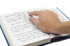 Finger pointing to Hebrew text in a siddur, a Jewish book of prayer.