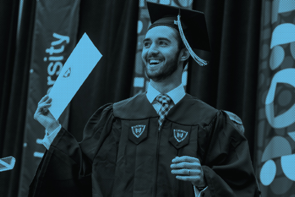 Young man crossing the commencement stage holding up his diploma